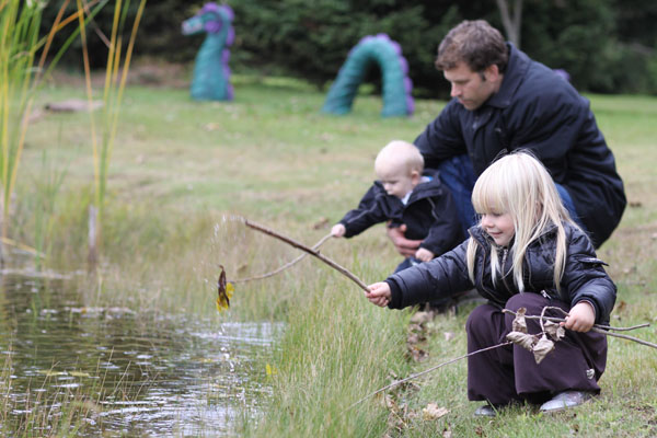 Elliot and Sienna playing by the pond with their sticks